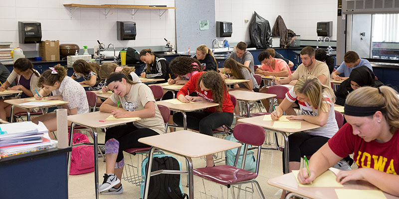 Students writing at desks in class